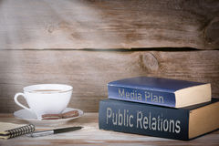 Public Relations and Media Plan. Stack of books on wooden desk Stock Photos