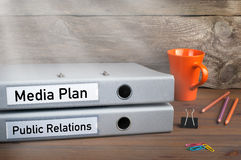 Public Relations and Media Plan - two folders on wooden office desk Stock Image