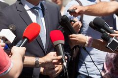 Public relations - PR. Media interview. News conference. Press interview. Broadcast journalism. Microphone Royalty Free Stock Image