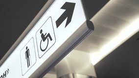 Public restroom signs. Public restroom illuminated signs with a disabled access symbol in the airport. Graphic design in public place stock video footage