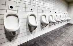 Public restroom. Modern public restroom - urinals in a row Royalty Free Stock Image