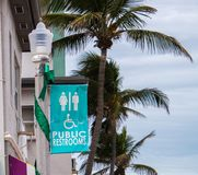 Public restroom sign with palm trees stock photo