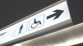 Public Restroom Signs. Public restroom illuminated signs with a disabled access symbol in the airport in slow motion. Graphic design in public place stock footage