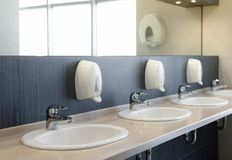 Public restroom with sinks faucets and mirror. Shallow DOF Royalty Free Stock Image