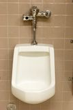 Public Restroom Urinal. Modern wall-attached urinal in a public bathroom. Sensor provides automatic flushing stock photos