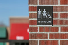 Public restrooms sign. Both genders and handicap accessible with wheelchair logo and braille Stock Photos