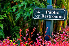 Public Restrooms Sign. A public restroom sign points out the way forpeople as they pass by.  The sign is surrounded by tropical plants from the red to green Stock Photography