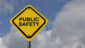 Public safety sign. Yellow traffic caution sign with black text graphics public safety against blue skies with drifting clouds stock footage