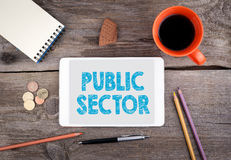 Public Sector. Tablet device on a wooden table. Public Sector. Text on tablet device on a wooden table Royalty Free Stock Image