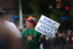 Public Servants Aren't Royalty. A man carries a sign protesting public servants in the Gay Pride Parade - Des Moines, Iowa Royalty Free Stock Photos
