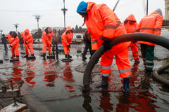 Public service workers. BUCHAREST, ROMANIA, DECEMBER 1, 2014: Public service workers are working on sewage after heavy precipitations in Bucharest stock images