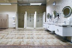 Public shower interior with everal showers. Toilet sink and lockers in locker room in luxury fitness spa centre Royalty Free Stock Photography