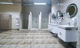 Public shower interior with everal showers. Toilet sink and lockers in locker room in luxury fitness spa centre Stock Photos
