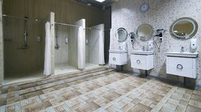 Public shower interior with everal showers. Toilet sink and lockers in locker room in luxury fitness spa centre Royalty Free Stock Photo