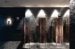 Public showers with wooden divider wall and dark t Royalty Free Stock Image