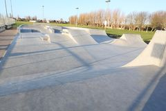 Skate park generic concrete ramps outside with blue sky Royalty Free Stock Photography