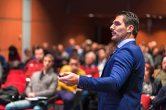 Public speaker giving talk at Business Event. Speaker giving a talk on corporate Business Conference. Audience at the conference hall. Business and Royalty Free Stock Images