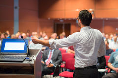 Public speaker giving talk at Business Event. Speaker giving a talk on corporate Business Conference. Audience at the conference hall. Business and Stock Images