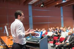 Public speaker giving talk at Business Event. stock image