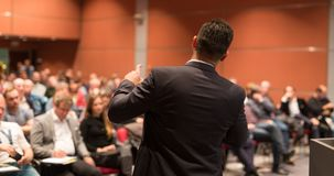 Public speaker giving talk at Business Event. Speaker giving a talk on corporate Business Conference. Audience at the conference hall. Business and Royalty Free Stock Image