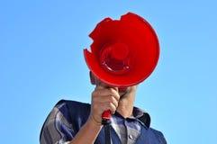 Public speaking. A man speaking through a broken megaphone Royalty Free Stock Photos