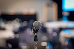 Public speaking in conference. Close up picture of a microphone in a conference room during meeting stock image