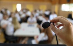 Free Public Speaking Fear. Person About To Speak Into A Small Microphone In Front Of A Large Crowd Stock Photography - 185432802