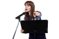 Public Speaking Female Pointing At Viewer. Girl in shiny dress speaking on a microphone in a podium on white background stock photography