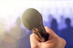 Public speaking and giving speech concept. Hand holding microphone in front of a crowd of silhouette people with lens flare and sun light leak bokeh. Singing royalty free stock images
