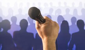 Public speaking and giving speech concept. Hand holding microphone in front of a silhouette audience and crowd of people. Singing to mic in karaoke or talent Stock Photography