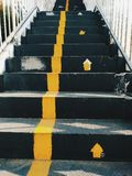 Public staircase with yellow lines to divide the way up and the way down / Signs of the way to up stairs but have no signs to way royalty free stock photos