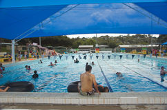 Public Swimming Pool. 50 metre outdoor public swimming pool of Newmarket, Brisbane, Australia, on a hot summer weekend day; open swimming pools with shade sails Stock Image