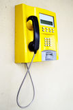 Public telephone. Yellow public telephone close-up on the wall royalty free stock image