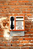 Public telephone. Orange public telephone on a red brick wall Royalty Free Stock Photo