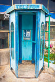 Public telephone booth. Old and rusty vintage blue public telephone booth Royalty Free Stock Images