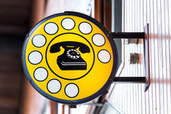 Public telephone indicated in the cartel Stock Images