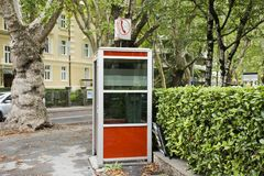 Public telephone on pathway beside traffic road in small alley stock photos