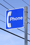 Public Telephone Sign. Phone symbol on a blue painted sign with white surround on metal post with utility wires in the background Royalty Free Stock Image
