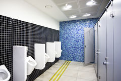 Public toilet with cubicles and urinals Royalty Free Stock Image