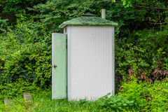 Public toilet with door open in wooded area. Old white public toilet with door open sitting at edge of a forested region on a mountainside in South Korea stock image