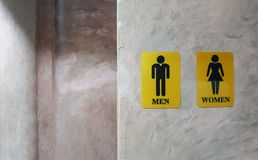 Public toilet of men and women. Sign of lady and gentleman washroom called wc. Mixed gender symbol toilet and restroom behind con. Crete wall decorate by vintage stock images