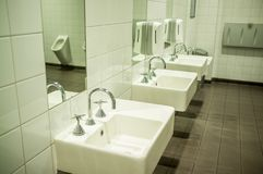 Public toilet with white stylish sinks. Male public toilet with white stylish sinks and urinal reflecting in mirror stock photos