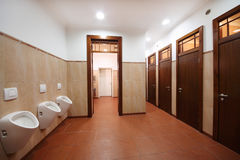 Public toilet. With white urinals, red tiles and brown wooden doors Stock Image