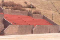Public toilet in a wooded area. Bleachers at a football field made of red brick and concrete built on the side of a hill royalty free stock images