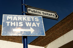 Public Toilets and Markets Sign. Public Toilets direction sign and markets this way sign with a blue sky and no people Royalty Free Stock Photos