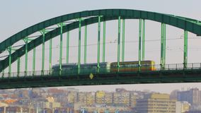 Public traffic on the Sava tram bridge in Belgrade. Green tram crossing over the bridge stock footage