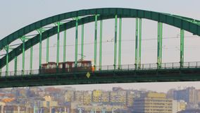 Public traffic on the Sava tram bridge in Belgrade. Red tram crossing over the bridge.  stock video footage