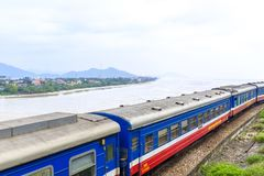Public train in Vietnam. A public train in central Vietnam with the Lang Co Bay in the background stock photo