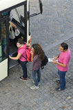 Public transport and bus passengers, Portugal. Transportation of people by a bus company. Aerial view of Young women, girls, youth and a man steps into a bus at Royalty Free Stock Photo
