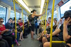 Public transport commuters in train. Public transport commuters sit in Perth train travelling to the northern suburbs royalty free stock image